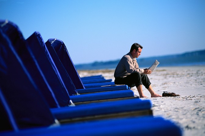 Man Reading Newspaper at Beach